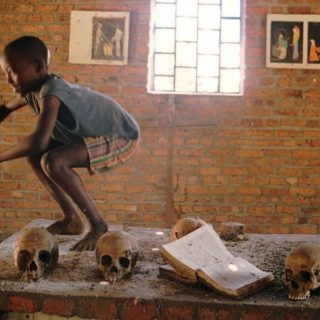 Flanked by the skulls of the dead, a Rwandan boy jumps down from the church altar he had been standing on, at the site of a massacre inside the Catholic Church of Ntarama, in rural Rwanda, Wednesday, August 6, 1997. Several thousand Tutsi people were murdered inside the church during the 1994 genocide, which currently is being left as it was found, as a memorial to the horror. (AP Photo/Brennan Linsley)